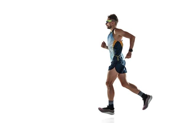 Athlète masculin de triathlon en cours d'exécution isolé sur fond de studio blanc