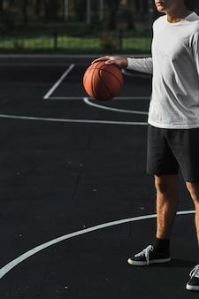 Athlète méconnaissable rebondissant sur le terrain de basket