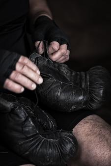 L'athlète met des gants de boxe en cuir noir