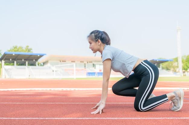 Athlète mignon asiatique sur une piste de course est prêt à courir,