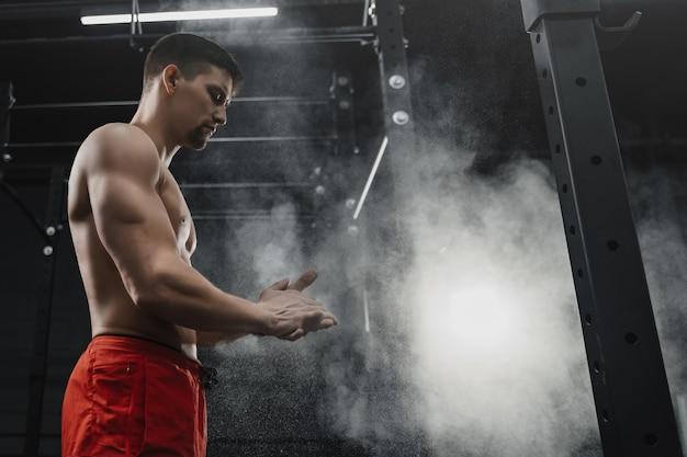 Athlète musclé crossfit frappant des mains et se préparant à l'entraînement au gymnase. concentrez-vous sur la poudre de craie de poussière. concept de sport. copier l'espace