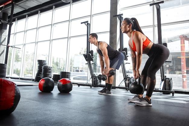 Un athlète musclé faisant de l'exercice au gymnase. gymnastique, entraînement, flexibilité d'entraînement de fitness. mode de vie actif et sain, jeunesse, musculation. faire des exercices ensemble, entraîner le haut du corps.