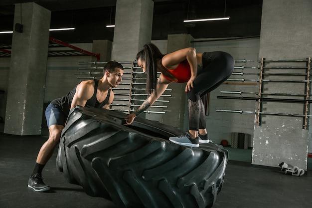 Un athlète musclé faisant de l'exercice au gymnase. gymnastique, entraînement, flexibilité d'entraînement de fitness. mode de vie actif et sain, jeunesse, musculation. faire des exercices ensemble, s'entraîner avec le pneu.