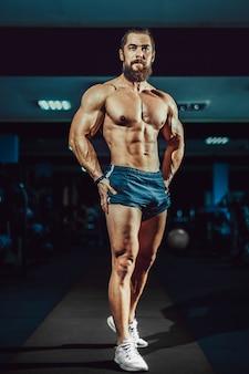 Athlète musclé homme bodybuilder posant dans une salle de sport.