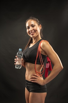 Athlète musclé jeune femme avec une corde à sauter sur fond noir