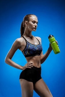 Athlète musclé jeune femme avec une eau sur bleu