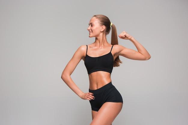 Athlète musclé jeune femme sur fond gris