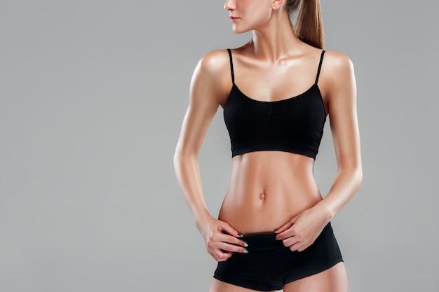 Athlète musclé de jeune femme sur fond gris