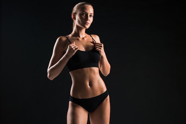 Athlète musclé de jeune femme sur fond noir