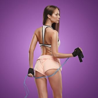 Athlète musclé jeune femme posant au studio sur fond lilas avec une corde