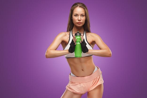Athlète musclé de la jeune femme posant au studio sur fond lilas avec de l'eau potable