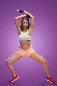 Athlète musclé jeune femme posant au studio sur fond lilas