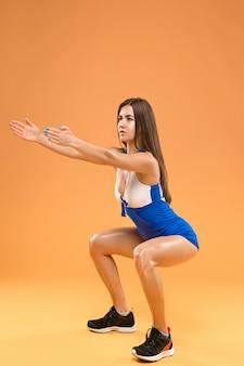 Athlète musclé jeune femme posant au studio sur fond orange