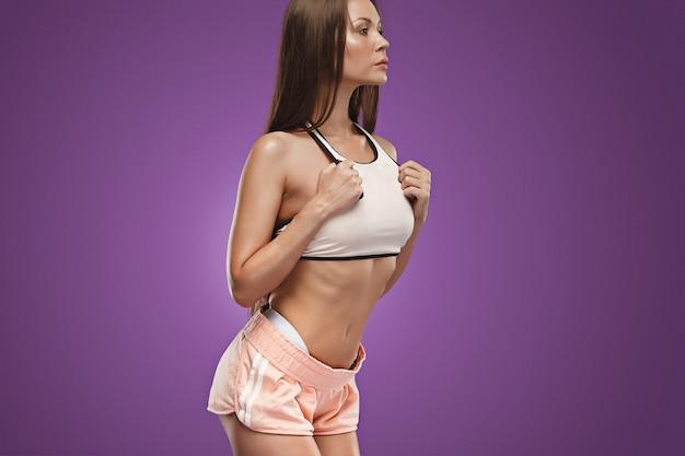 Athlète musclé jeune femme posant sur l'espace lilas