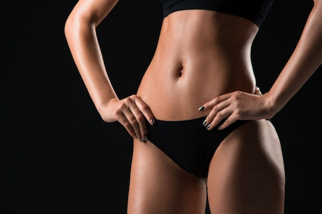 Athlète musclé de la jeune femme posant sur fond de studio noir