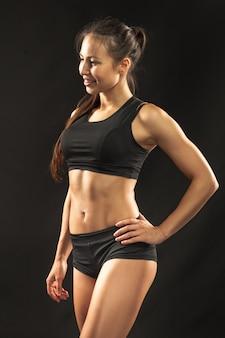 Athlète musclé jeune femme regardant à huis clos sur fond noir