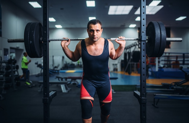 Athlète musclé pose au stand avec haltères