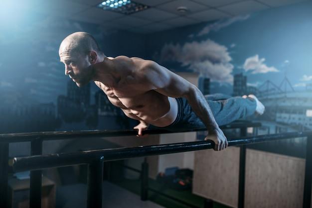 L'athlète musculaire fait des exercices d'équilibre horizontal sur des barres de gymnastique dans une salle de sport.