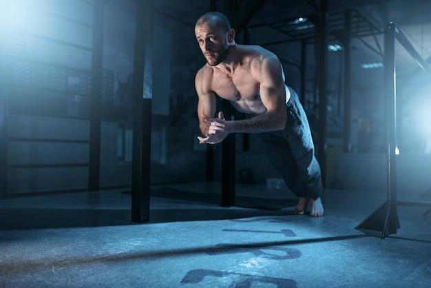 L'athlète musculaire fait des exercices de pompes dans le gymnase. gymnaste solide à l'entraînement