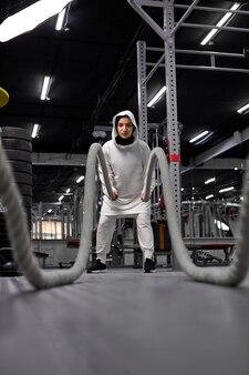 Athlète musulmane cross fit en hijab travaillant avec de lourdes cordes à la recherche de déterminad et d'entraînement fonctionnel concentré athlétisme fitness activité sportive renforcement de la confiance