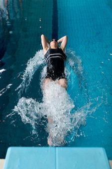 Athlète nageant dans la piscine plein coup
