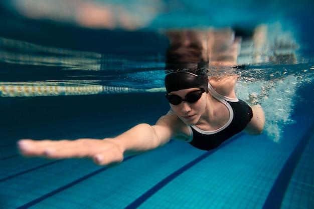 Athlète nageant sous l'eau avec casquette