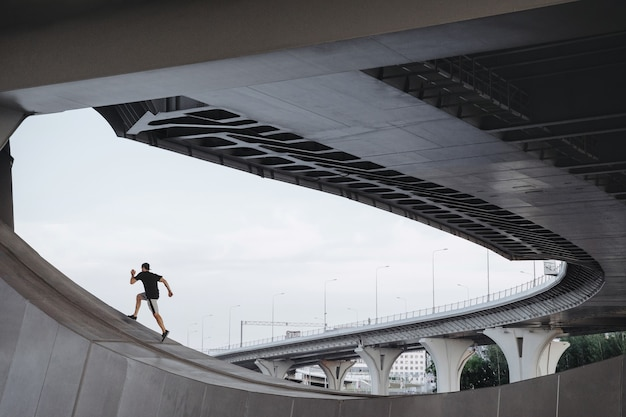 L'athlète de parkour monte le pont. freerunning en ville