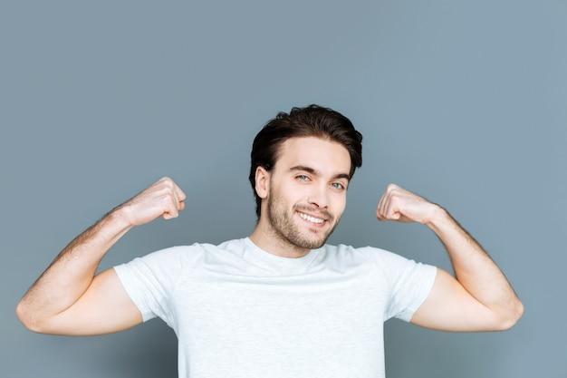 Athlète professionnel. joyeux homme brutal bien construit souriant et montrant son corps tout en profitant d'activités sportives