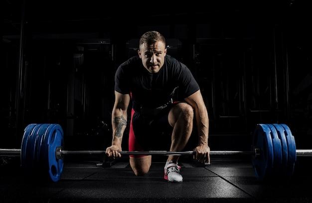 Athlète professionnel penché sur la barre et se prépare à soulever un poids très lourd.