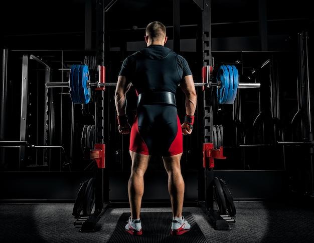 L'athlète professionnel se tient devant les barres avec une barre et est sur le point de s'accroupir avec elle. vue arrière