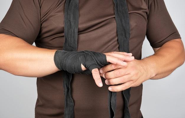 L'athlète se blottit dans des vêtements et enveloppe ses mains dans un bandage élastique en textile