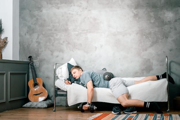 L'athlète se prélasse, se repose avec des haltères et reporte l'entraînement à la maison. le concept de proastination, de paresse sportive