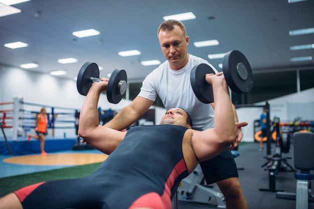 L'athlète se trouve sur un banc et fait de l'exercice avec un haltère sous le contrôle de l'instructeur