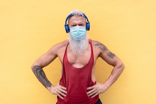 Athlète senior homme portant un masque médical pour la prévention des coronavirus tout en écoutant de la musique de liste de lecture