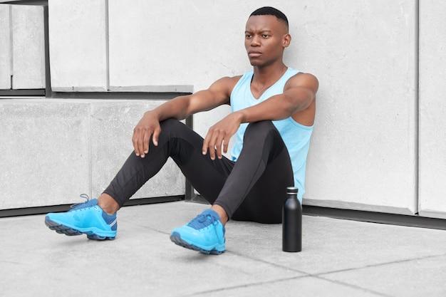 Un athlète sérieux et fort est assis près des marches, a une expression fatiguée, est épuisé par de longues heures d'entraînement cardio, monte dans les escaliers, une bouteille d'eau sportive près, se penche au mur, a un corps athlétique
