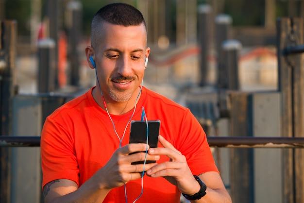 L'athlète souriant télécharge la musique sur un smartphone