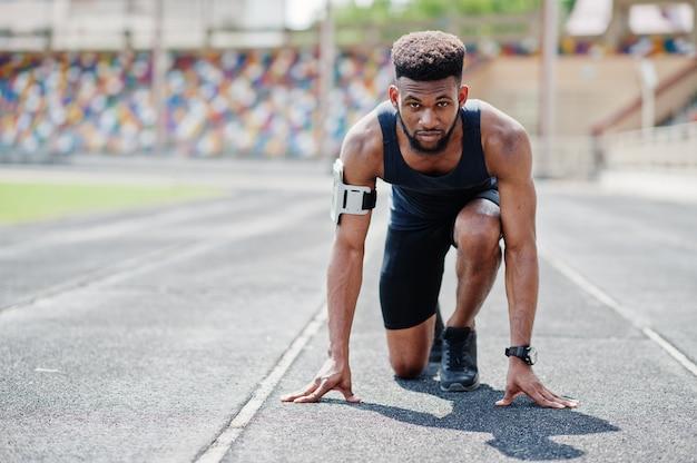 Athlète en sportswear racing seul sur une piste de course au stade