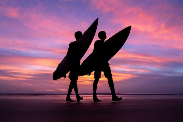Athlète de surf silhouette pendant le coucher du soleil à phuket en thaïlande