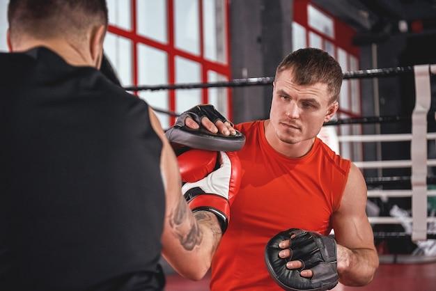 Athlète tatoué fort de boxe proche dans l'entraînement de vêtements de sport sur les pattes de boxe avec son partenaire