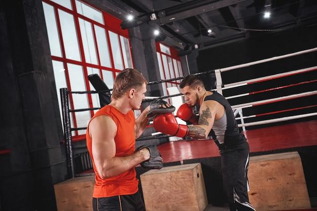 Athlète tatoué fort coup de poing dans l'entraînement de vêtements de sport sur pattes de boxe avec partenaire