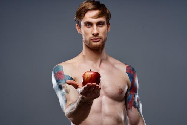 Athlète tatoué tenant une pomme rouge sur fond gris torse nu vue recadrée
