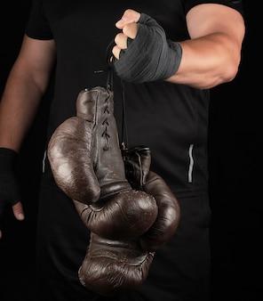 Athlète en tenue noire est titulaire de très vieux gants de boxe en cuir noir vintage