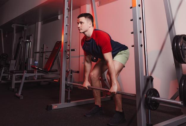 L'athlète tient une barre dans ses mains tout en se préparant à s'accroupir. musculation dans la salle de gym