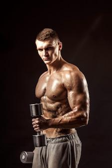 Athlète torse nu tatoué sérieux soulevant des haltères métalliques sur un mur sombre