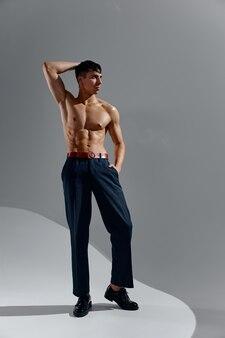 Athlète avec un torse pompé torse nu bodybuilder fitness jeans chaussures