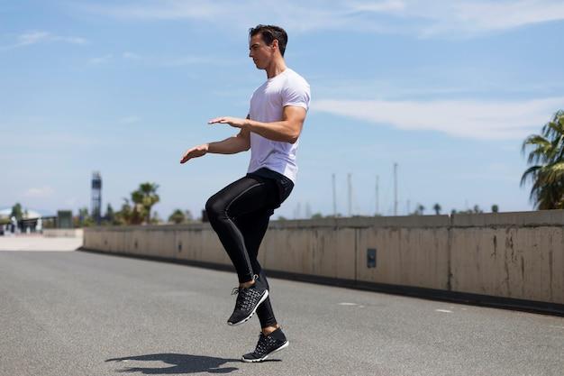 Athlète travaillant sur cross-fit sauter à l'extérieur.