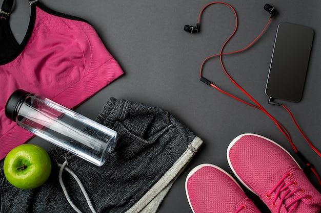 Athlètes avec baskets de vêtements féminins et bouteille d'eau sur fond gris