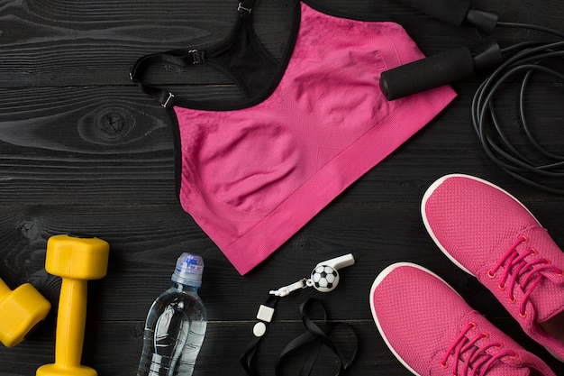Athlètes avec baskets de vêtements féminins et bouteille d'eau sur fond sombre