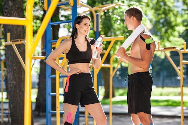 Athlètes caucasiens professionnels avec bande élastique de kinésiologie sur les corps, bel homme avec une serviette sur l'épaule et femme brune tenant de l'eau, posant sur un terrain de sport, parler et se reposer.
