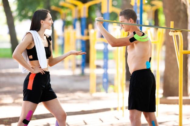 Athlètes caucasiens professionnels bel homme formation à l'aide d'une bande de résistance et d'une femme brune avec un enregistrement kinésiologique sur les corps